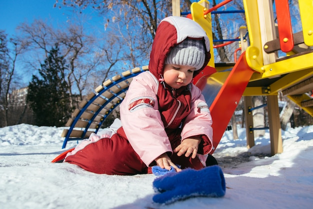 Little baby plays in the playground in winter