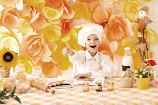 작은 아기는 부엌에서 맛있는 요리를 준비하고 엄지 손가락을 보여줍니다.