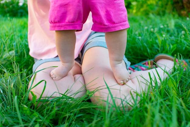 Ножка малыша впервые ступила на зеленую траву. счастливая семья на природе