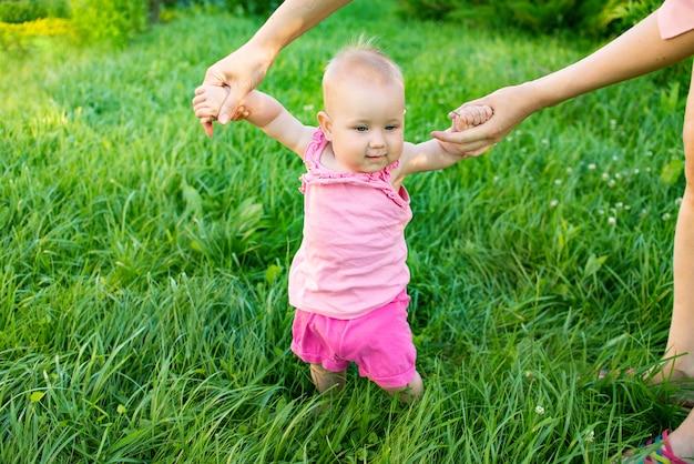 Ножка маленькой девочки впервые ступила на зеленую траву. счастливая семья на природе