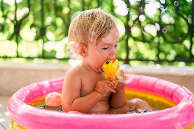 작은 아기는 작은 풍선 수영장에 앉아 장난감을 갉아 먹습니다.
