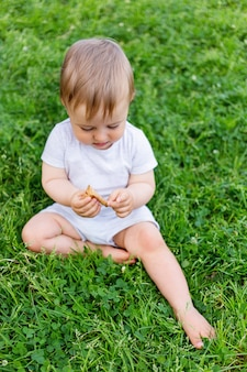 Little baby sitting on grass. kid is staring on fallen leaf. outdoor activity for kid.