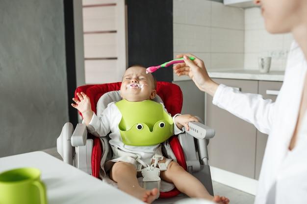 母親がスプーンで彼に餌をやろうとする間、口の近くの残り物が赤ちゃんの椅子に座っている小さな赤ちゃんは泣き、食事を拒否します。