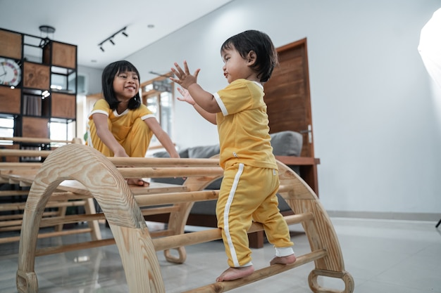 Маленький ребенок стоит в игрушках-треугольниках пиклер и хлопает в ладоши