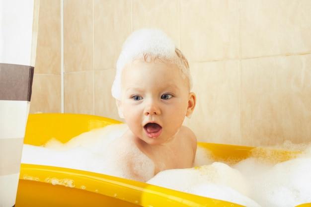 小さな赤ちゃんは、泡と泡のある黄色いお風呂でお風呂に入ります。