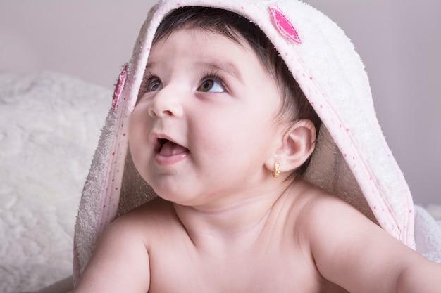 목욕이나 샤워 후 침대에서 휴식 흰색 목욕 타월을 입고 작은 아기. 어린이를위한 보육