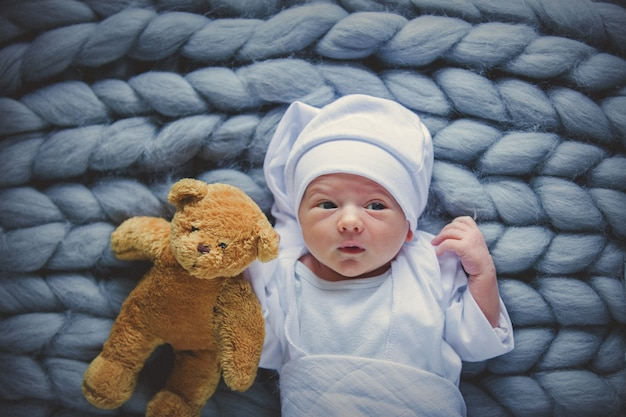 Little baby wearing a white clothes and hat with taddy bear