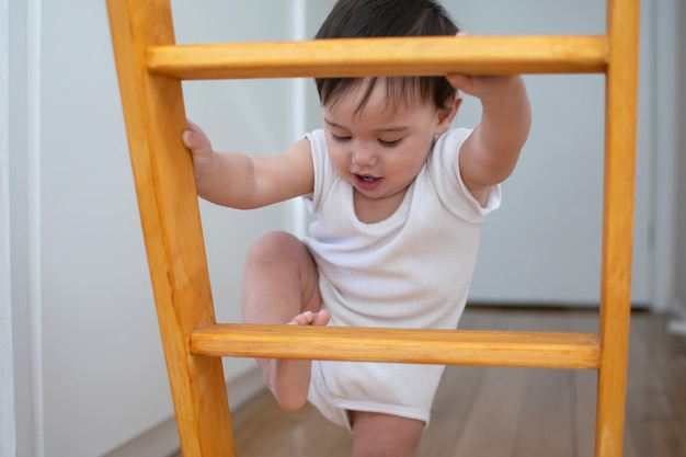 Little baby in white body suit is trying to climb up the the wooden indoor ladder