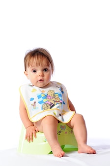 Little baby with bib sitting on potty