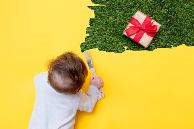 Маленький ребенок с праздничным подарком на желтых и зеленых травах