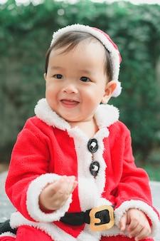 바닥에 산타 클로스 복장으로 작은 아기