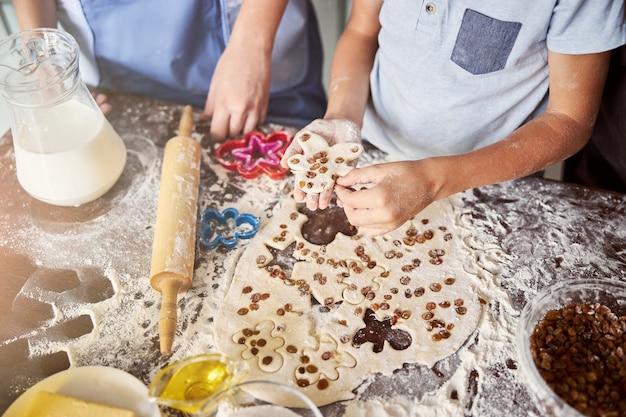 Маленькие пекари вырезают из теста печенье в форме человечков