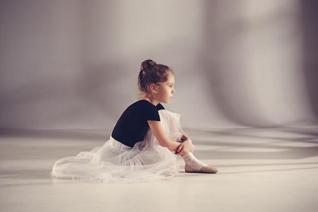 La piccola ballerina balerina sul muro grigio