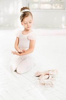 La piccola balerina in tutù bianco in classe alla scuola di balletto
