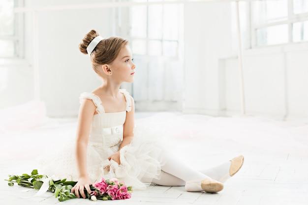 Piccola balerina in tutù bianco in classe alla scuola di balletto