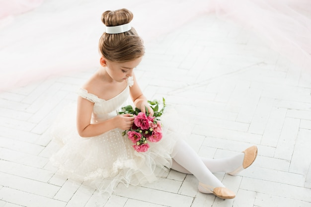 The little balerina in white tutu in class at the ballet