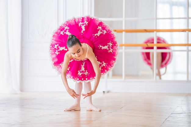 Little ballerina in a bright pink tutu stands in a pose in a beautiful white hall