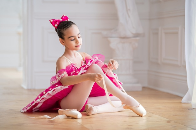 Little ballerina in bright pink tutu tying shoes