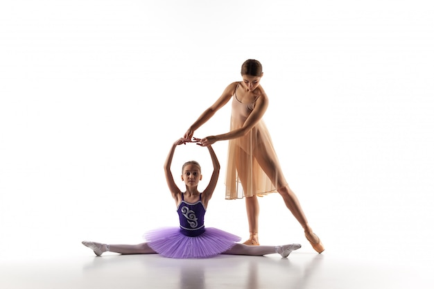 Little ballerina dancing with personal ballet teacher in dance studio