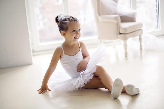 白いチュチュドレスの服を着た小さなバレリーナの女の子2年