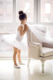 Маленькая балерина девочка 2 года в студии в белом платье-пачке стоит в кресле и смотрит в окно