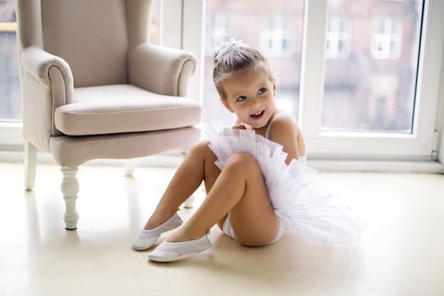Маленькая балерина девочка 2 года в студии в белом платье-пачке