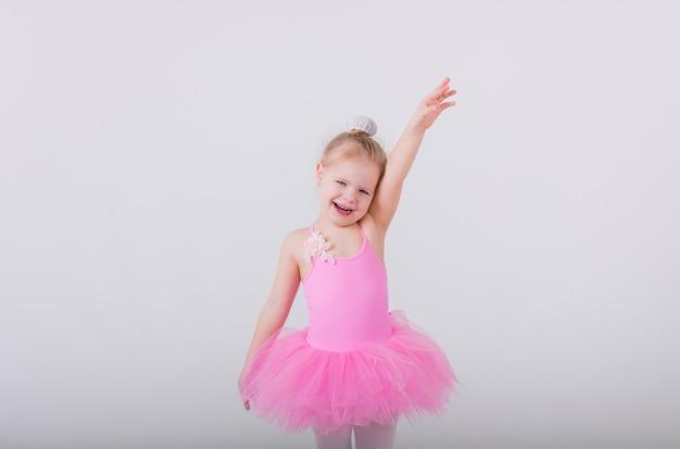 Маленькая балерина в розовом платье с юбкой-пачкой стоит в позе на белой стене