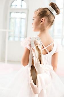 투투를 입은 작은 발레리나 소녀. 흰색 스튜디오에서 클래식 발레를 춤추는 사랑스러운 아이.