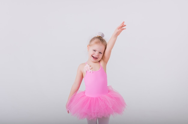 Little ballerina girl in a pink dress with a tutu skirt stands in a pose on a white wall