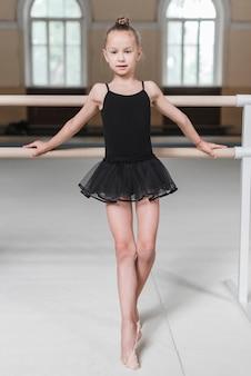 Little ballerina girl standing in front of barre
