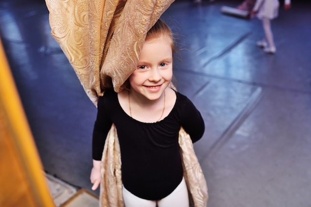 Little ballerina girl in a training swimsuit smiles hiding behind a curtain