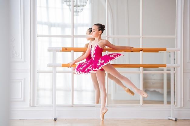 Маленькая балерина в яркой малиновой пачке стоит у барре в арабской позе