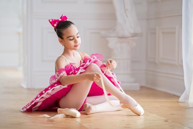 Маленькая балерина в ярко-розовых туфлях-пачках завязывает