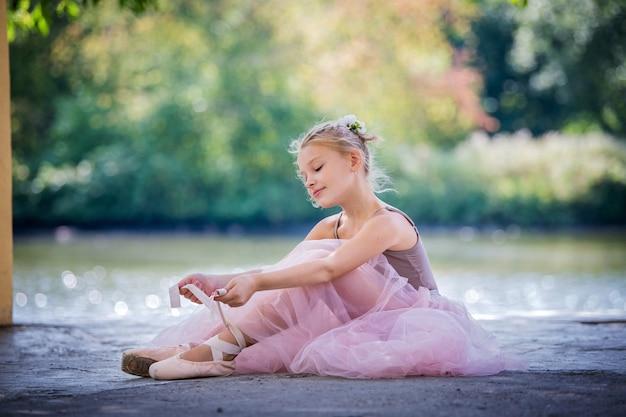 長いバレエスカートのピンクの小さなバレリーナが床に座って、ポアントリボンを結ぶ