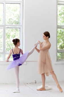 Little ballerina posing at ballet barre with personal teacher in dance studio