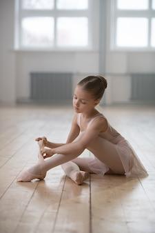 Маленькая балерина сидит на полу и готовится к занятиям в танцевальной студии