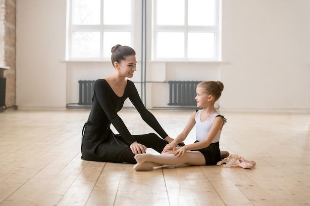 Маленькая балерина сидит на полу и разговаривает со своим учителем балета, они отдыхают после тренировки