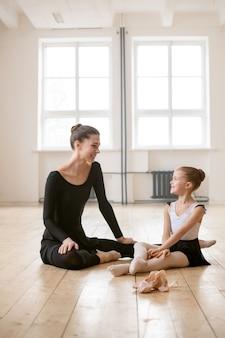 床に座って、トレーニング後に休んでいるバレエの先生と話している小さなバレリーナ