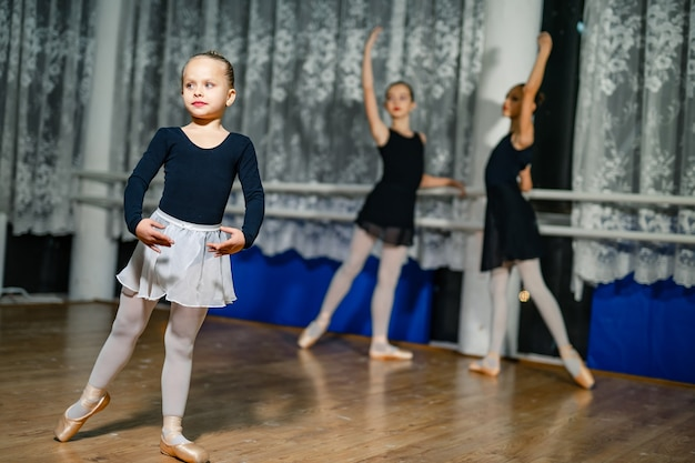 작은 발레리나가 두 명의 발레리나와 함께 흐릿한 배경에 손을 얹고 포즈를 취하고 있습니다. 댄스 스튜디오에서 수업 중 연습하는 소녀들. 확대