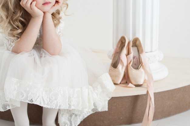 Little ballerina in white dress sitting next to large pointe shoes