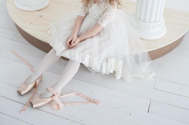 Little ballerina in a white lush dress wears pointe shoes