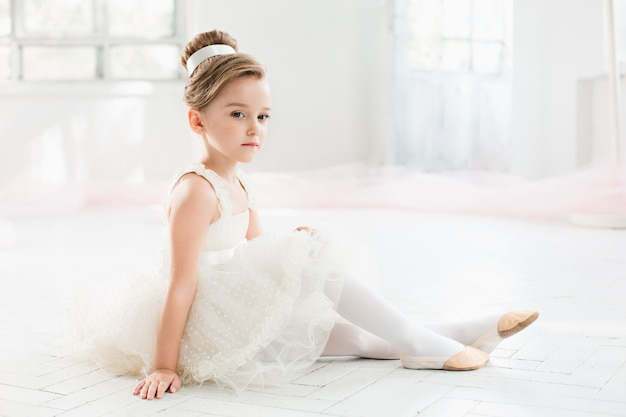 Little ballerina in white tutu at the ballet school