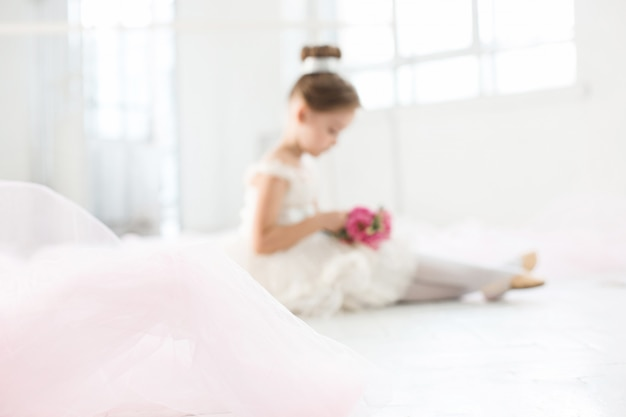 Little ballerina in white tutu at the ballet school