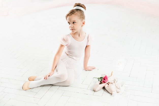 Little ballerina in white tutu in class at the ballet school
