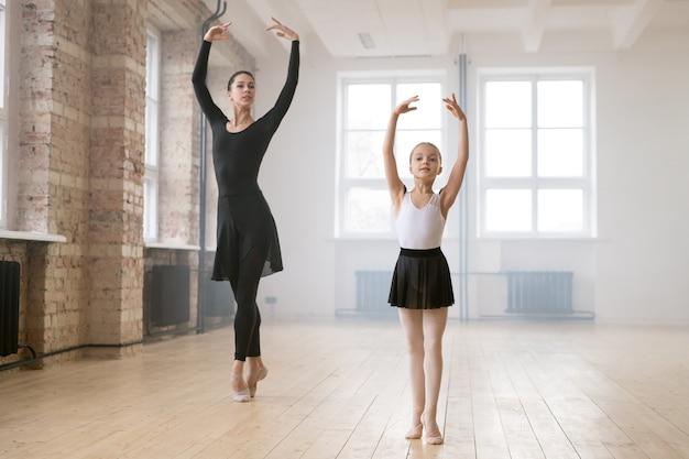 ダンススタジオでの授業中にトレーナーと一緒に踊る小さなバレリングガール
