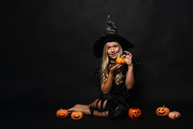 Little barefoot witch showing jack-o-lantern