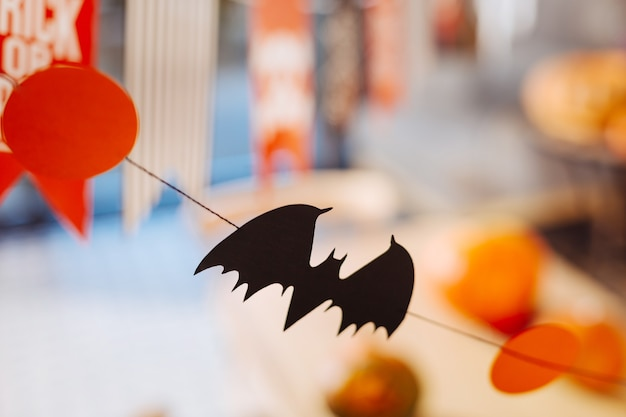 Little bat. close up of little black bat made out of paper hanging above the halloween celebration table