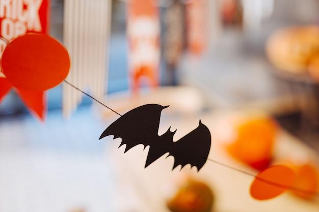 リトルバット。ハロウィーンのお祝いのテーブルの上にぶら下がっている紙で作られた小さな黒いコウモリのクローズアップ