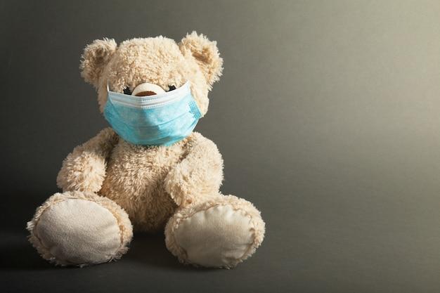 小さなクマがコロナウイルスcovid-19の保護用フロアマスクの黒い部屋に座っている