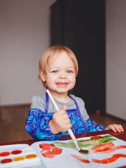 小さな美しい女の赤ちゃん、アルバムの水彩絵の具でペイント